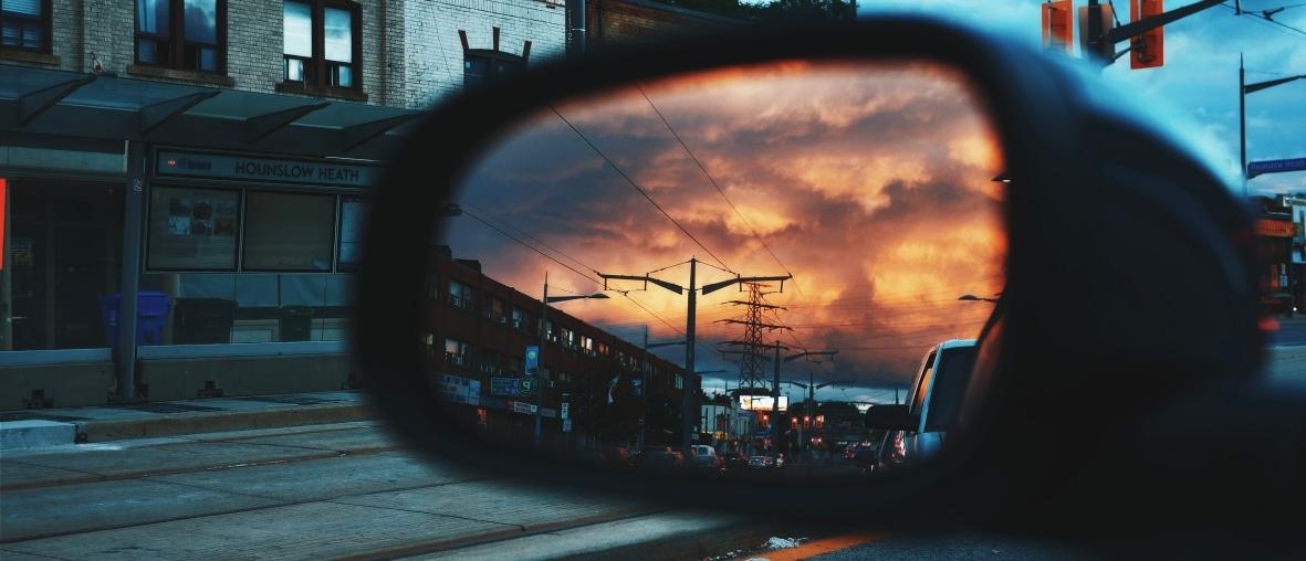 rétroviseur voiture soleil couchant sur la ville