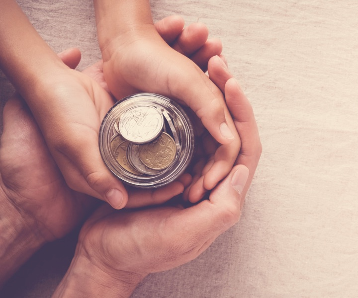mains d'enfant et d'adulte qui tiennent un pot en verre avec des euros